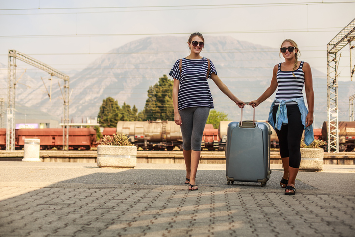 Low angle, front view of two young women standing at the train station, holding same piece of the luggage and smiling as a sign of excitement about the trip ahead of them.